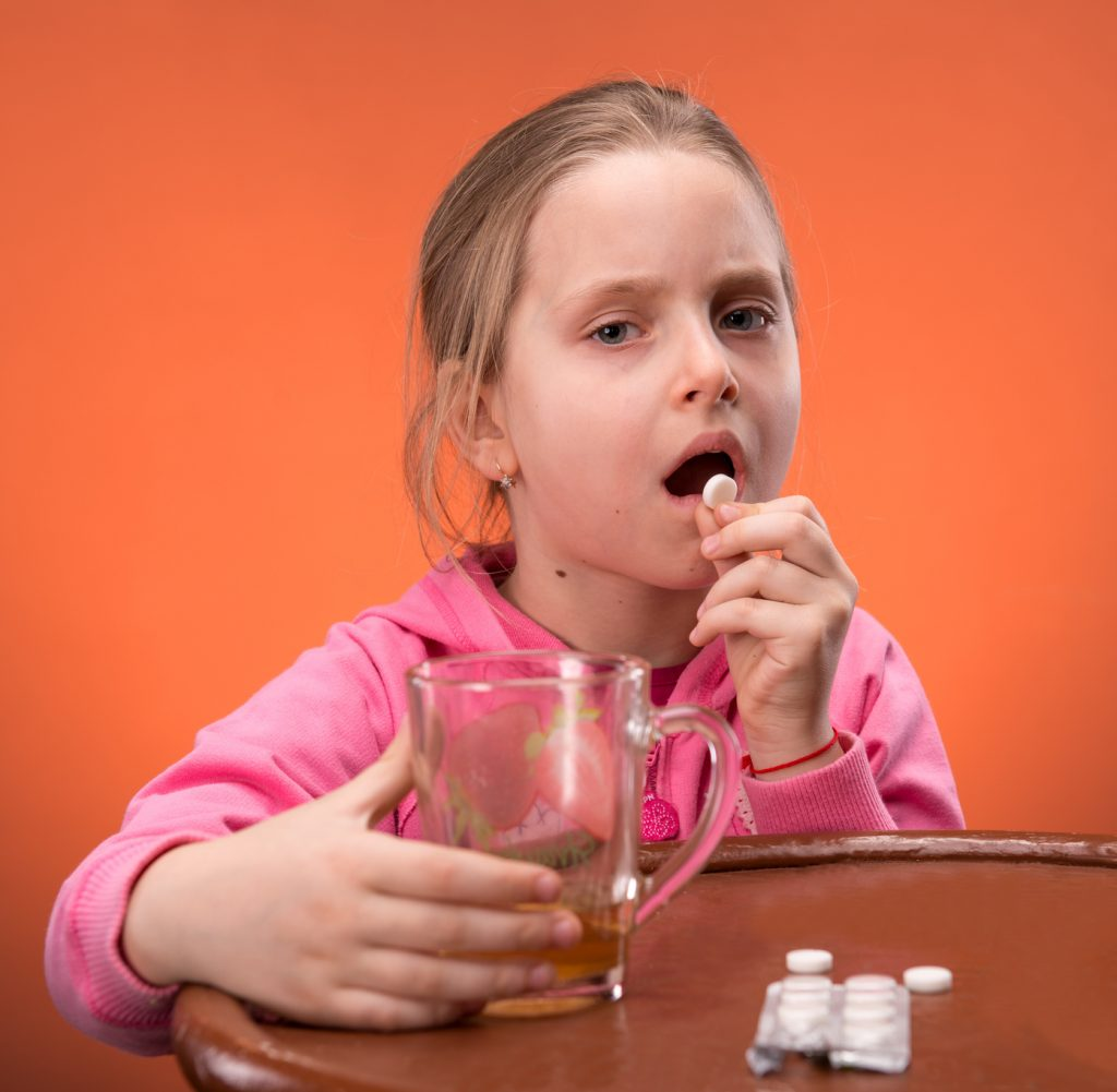 Girl looks very upset at the thought of taking her medicine